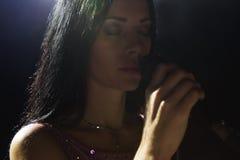 Ritratto di bella donna di canto su fondo scuro fotografia stock