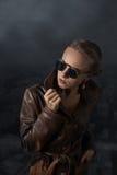 Ritratto di bella donna in cappotto ed occhiali da sole di cuoio marroni immagine stock libera da diritti