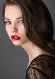 Ritratto di bella donna castana in vestito nero e labbra rosse Fotografia Stock