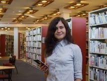 Ritratto di bella donna caucasica sorridente che per mezzo dello Smart Phone moderno all'interno Fotografia Stock Libera da Diritti