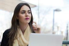 Ritratto di bella donna che per mezzo del computer portatile al caffè Fotografia Stock Libera da Diritti