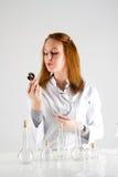 Ritratto di bella donna che posa sul fondo grigio con la lampadina Immagine Stock
