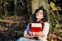 Ritratto di bella donna che si appoggia un albero con il libro nel parco di autunno Fotografie Stock