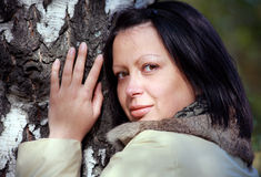 Ritratto di bella donna che si leva in piedi al lato di un pino Fotografia Stock