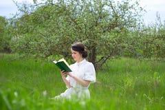 Ritratto di bella donna che si siede con il libro sul prato di estate Fotografia Stock Libera da Diritti