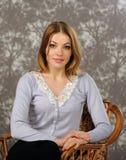 Ritratto di bella donna che si siede su una presidenza Immagine Stock