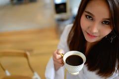 Ritratto di bella donna che tiene una tazza di caffè in sua mano nella caffetteria del fondo della sfuocatura fotografia stock