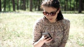 Ritratto di bella donna che utilizza smartphone nel parco Movimento lento 50FPS archivi video