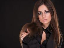 Ritratto di bella donna con capelli lunghi su fondo nero Fotografia Stock
