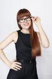 Ritratto di bella donna con capelli rossi in vetri neri ed in vestito nero Fotografie Stock Libere da Diritti