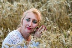 Ritratto di bella donna con gli occhi verdi che si siedono nel giacimento di grano e nel mazzo dorati della tenuta di orecchie de fotografie stock