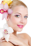 Ritratto di bella donna con il fiore dell'orchidea in suoi capelli. Bello Woman Face di modello. Pelle perfetta. Make-up.Makeup pr Fotografie Stock Libere da Diritti