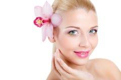 Ritratto di bella donna con il fiore dell'orchidea in suoi capelli. Bello Woman Face di modello. Pelle perfetta. Make-up.Makeup pr Fotografia Stock