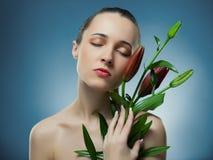 Ritratto di bella donna con il fiore rosso. Fotografie Stock