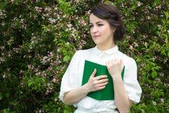 Ritratto di bella donna con il libro nel giardino di fioritura della molla Immagine Stock