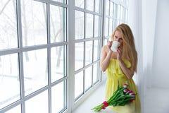 Ritratto di bella donna con il mazzo del tulipano e del tè della tazza alla finestra 8 marzo Copyspace Fotografie Stock