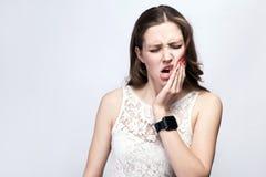 Ritratto di bella donna con le lentiggini e vestito da bianco ed orologio astuto con dolore di dente sul fondo di gray d'argento fotografia stock