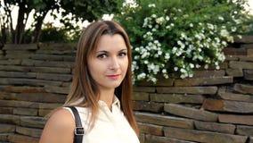 Ritratto di bella donna contro lo sfondo di una parete dalle pietre e dai fiori donna che cammina nella pietra stock footage