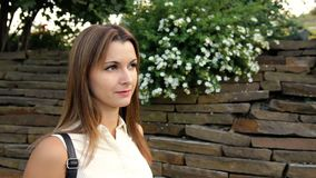 Ritratto di bella donna contro lo sfondo di una parete dalle pietre e dai fiori donna che cammina nella pietra video d archivio