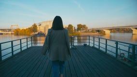 Ritratto di bella donna d'avanguardia dei pantaloni a vita bassa della corsa mista Gode della vista del fiume della città che cam archivi video