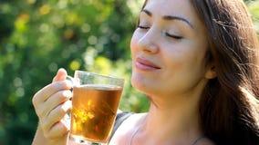 Ritratto di bella donna del primo piano che beve il tè con la menta fresca archivi video