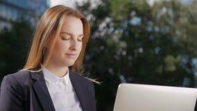 Ritratto di bella donna di affari che per mezzo del PC del computer portatile fuori del centro di affari video d archivio