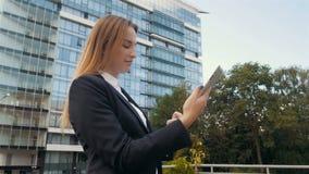 Ritratto di bella donna di affari che per mezzo del PC della compressa fuori del centro di affari video d archivio