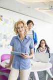 Ritratto di bella donna di affari che tiene compressa digitale con i colleghi nel fondo all'ufficio creativo immagini stock