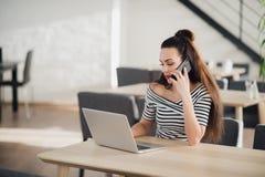 Ritratto di bella donna di affari che tiene un telefono mentre godendo del caffè caldo nel caffè Femmina attraente adulta Immagine Stock Libera da Diritti