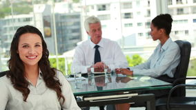 Ritratto di bella donna di affari con i colleghi nel fondo Fotografia Stock Libera da Diritti