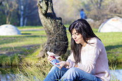 Ritratto di bella donna di risata che conta i suoi soldi nel parco Immagine Stock