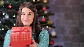 Ritratto di bella donna europea che dà il contenitore di regalo nell'albero di Natale variopinto del bokeh del fondo stock footage