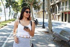Ritratto di bella donna latina con lo sguardo d'avanguardia facendo uso del telefono delle cellule mentre camminando fuori nel gi Immagine Stock Libera da Diritti