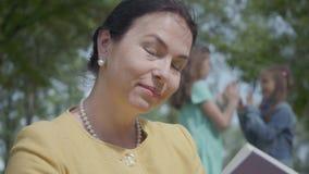Ritratto di bella donna matura graziosa che legge un libro e le sue nipoti adorabili per giocare insieme nel parco a archivi video