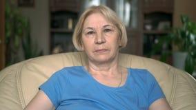 Ritratto di bella donna senior seria che si siede nella sedia a casa Avere buon rilassamento di tempo video d archivio
