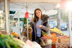 Ritratto di bella donna sorridente al mercato del ` s dell'agricoltore Immagine Stock
