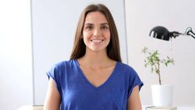 Ritratto di bella donna sorridente che esamina macchina fotografica in ufficio Immagini Stock