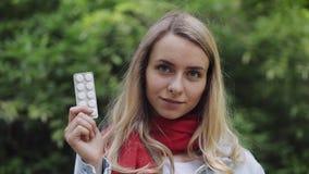 Ritratto di bella donna sorridente che indossa il blisterpack rosso della tenuta della sciarpa con le pillole nella sua condizion video d archivio