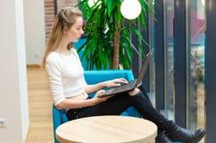 Ritratto di bella donna sorridente che si siede su una sedia comoda in un caffè con il computer portatile nero Studente grazioso  Immagine Stock Libera da Diritti