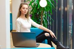Ritratto di bella donna sorridente che si siede su una sedia comoda in un caffè con il computer portatile nero Studente grazioso  Fotografia Stock