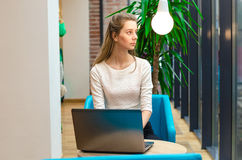 Ritratto di bella donna sorridente che si siede su una sedia comoda in un caffè con il computer portatile nero Studente grazioso  Fotografia Stock Libera da Diritti