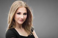 Ritratto di bella donna sorridente su fondo grigio Immagini Stock Libere da Diritti