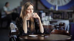 Ritratto di bella donna in un caffè o in un ristorante Una ragazza beve il tè o caffè e sogni circa qualcosa stock footage