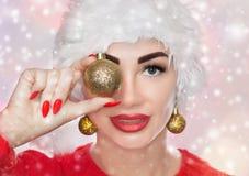 Ritratto di bella donna in un cappello rosso di Santa Claus ed in un maglione rosso tricottato che tengono una palla dorata di na fotografie stock libere da diritti