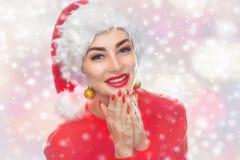 Ritratto di bella donna in un cappello rosso di Santa Claus ed in un maglione rosso tricottato sul fondo dei fiocchi di neve fotografie stock libere da diritti
