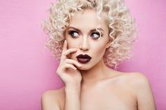 Ritratto di bella e ragazza di modello alla moda con gli occhi azzurri stupefacenti, con capelli biondi ricci e con il makeu lumi fotografia stock libera da diritti