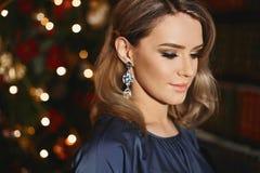 Ritratto di bella e ragazza di modello bionda alla moda con trucco luminoso e con gli orecchini d'avanguardia, nel vestito blu fotografie stock