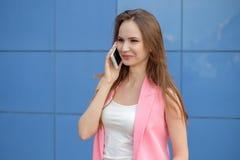 Ritratto di bella fine sorridente della giovane donna su con il telefono cellulare all'aperto fotografia stock libera da diritti