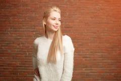 Ritratto di bella giovane bionda in rivestimento caldo bianco e jeans rossi che stanno su un fondo rosso del muro di mattoni Fotografia Stock