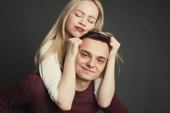 Ritratto di bella giovane coppia nell'amore che posa allo studio sopra fondo scuro Ragazza che si siede sulle spalle di un giovan Fotografie Stock